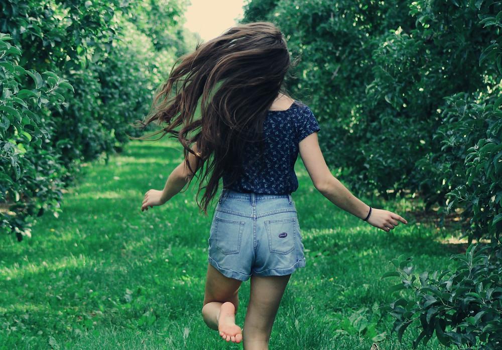 woman running through greenery