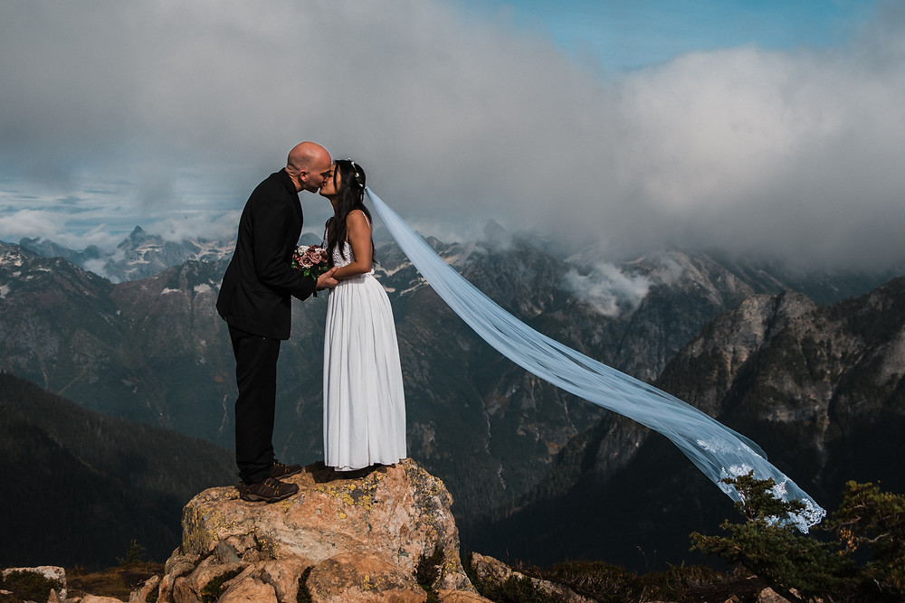 A couple kisses on top of a mountain on their elopement day in Washington