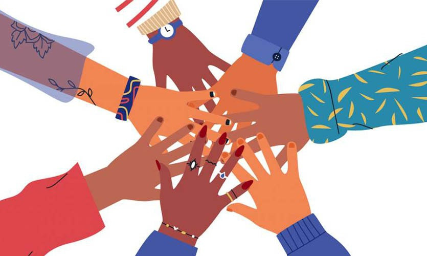 A group of diverse hands touching to show inclusion and diversity.