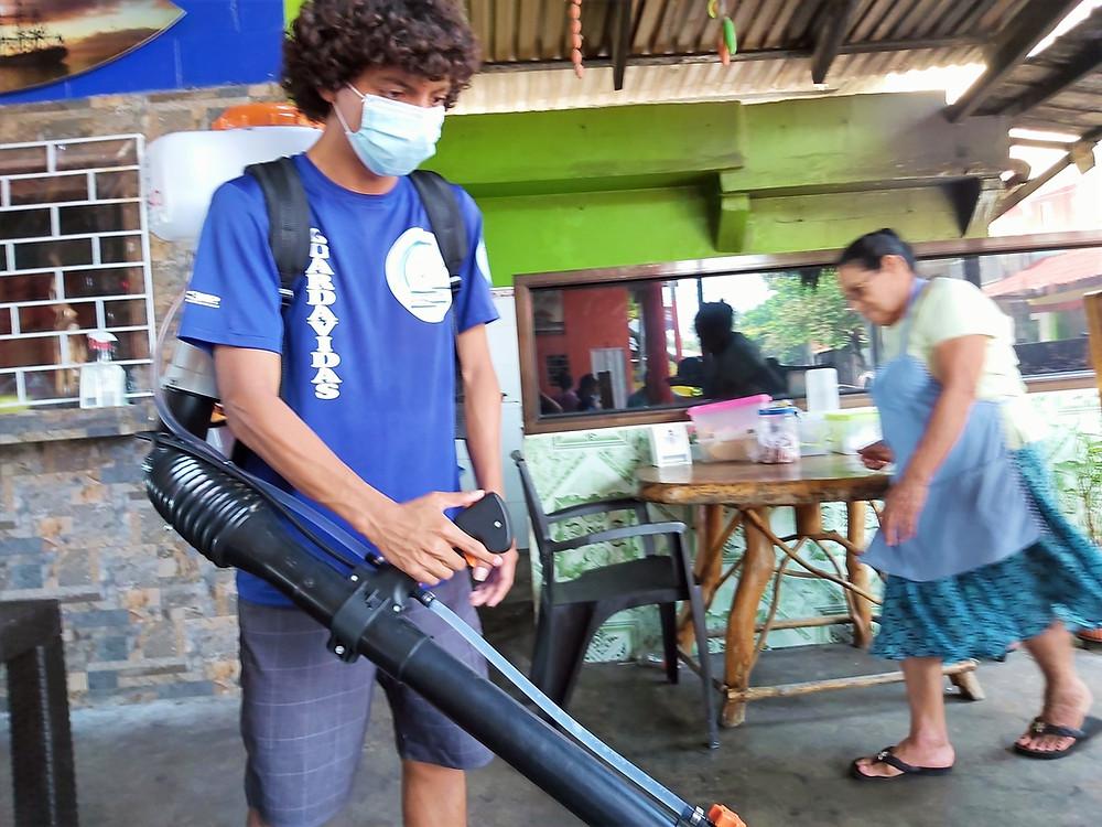 Guardavida aplicando amonio cuaternario en un rancho de la playa El Majahual