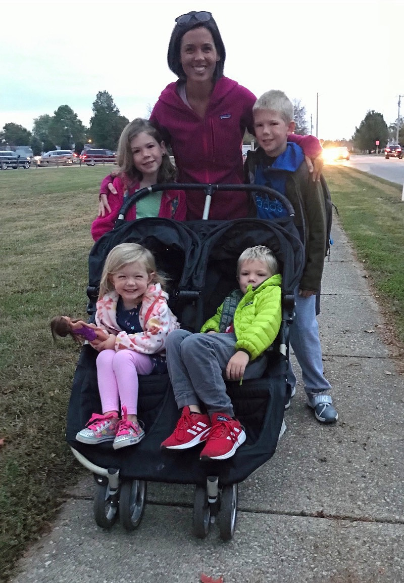 The Fitzsimmons family, pictured on their walk to school. Mom Lindsay and two older children walk, while the two younger children ride in the stroller.