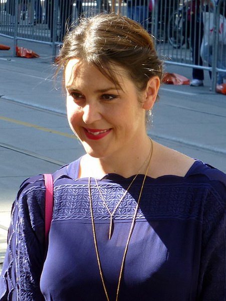 Melanie Lynskey at the premiere of The Meddler, 2015 Toronto Film Festival. She is wearing a purple top, red handbag, and has tied her light-brown hair behind hair back.