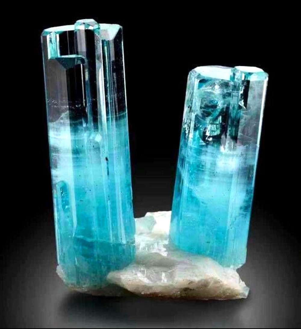 aquamarine rough crystal on a white host rock on a black background