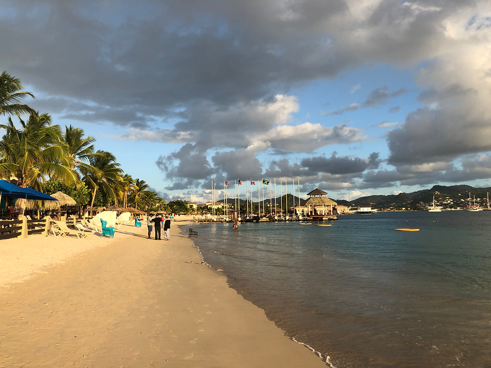 A long, beautiful sand beach with cabanas and over water villas in the distance in Saint Lucia