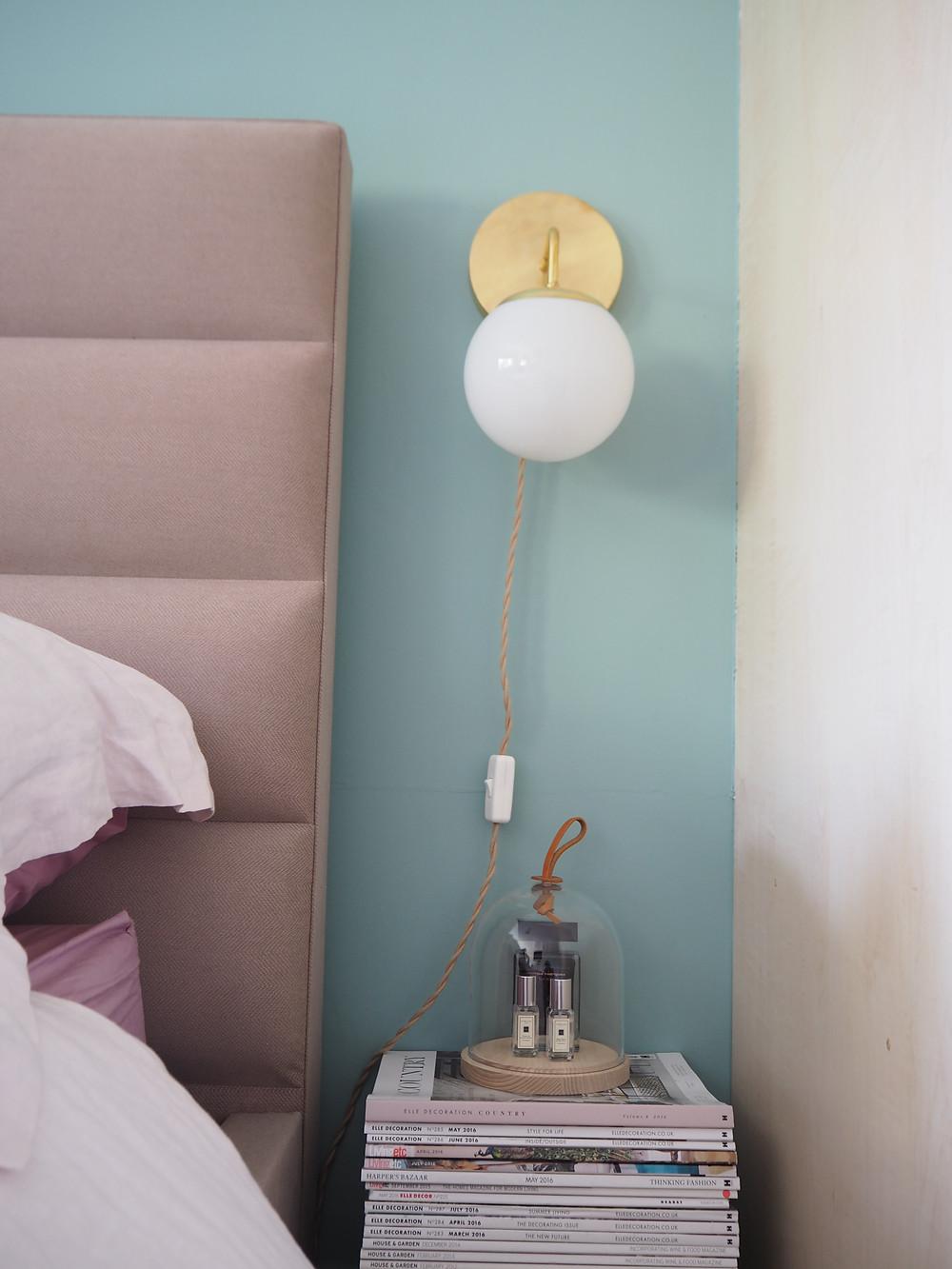 Wall colour IS Farrow & Ball DIX BLUE, Jenny Kakoudakis pink headboard and a brass side lamp, feminine bedroom decor