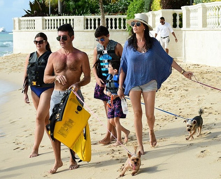 Simon Cowell and family walk the dogs on the beach in Barbados