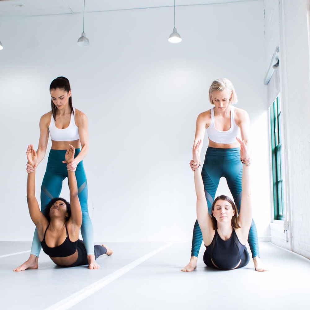 Jemma and Zhana stretching students in flexibility class