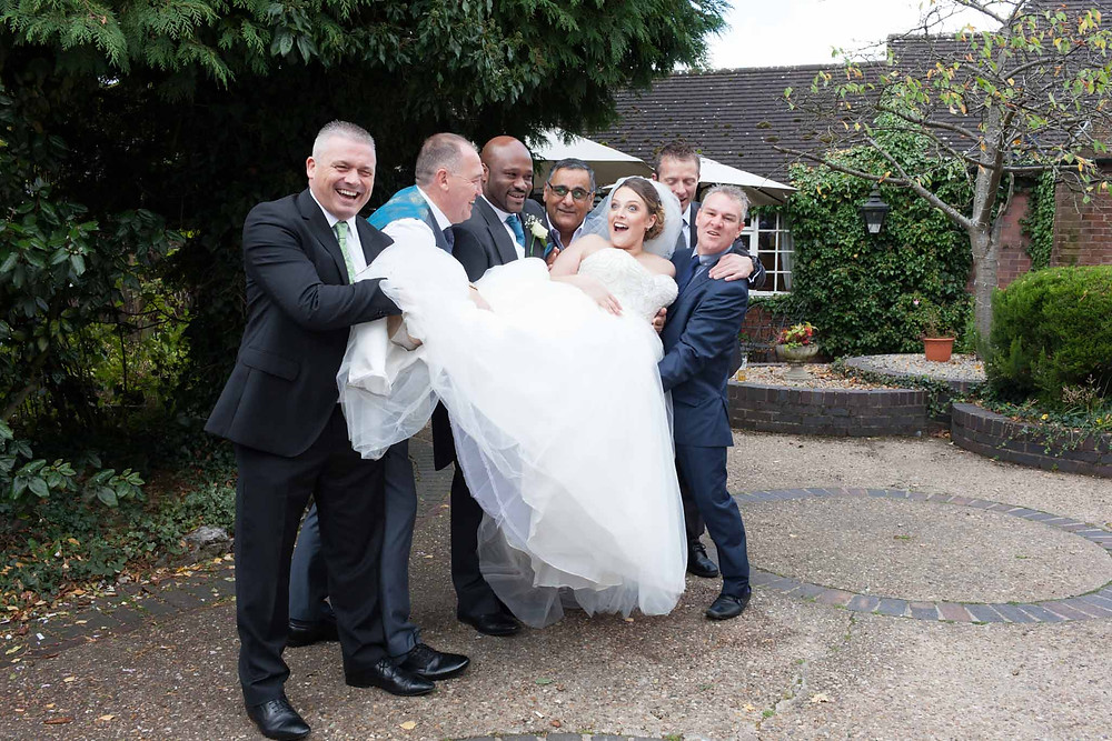 laughing bride being lifted by her groom and all the groomsmen
