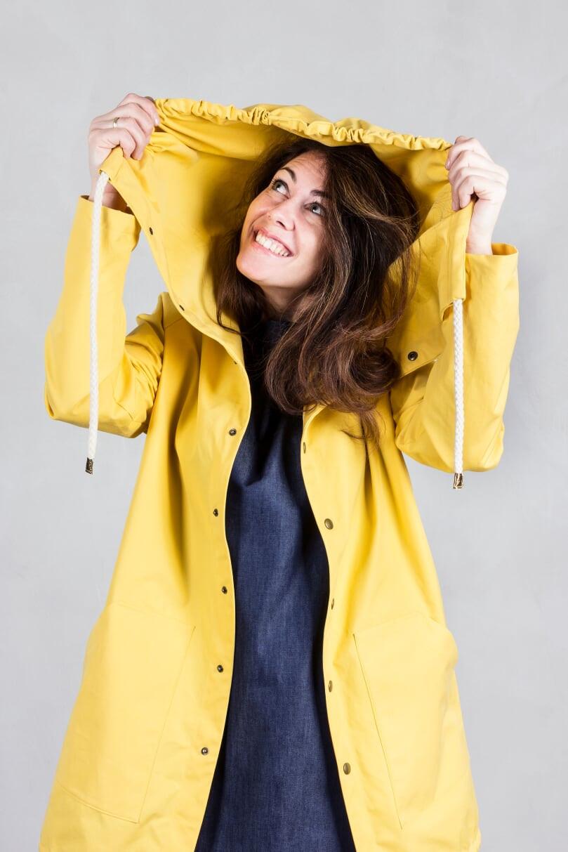 lachende Frau in einem gelben Bio Regenmantel von Cade Wien. Der Regenmantel ist natürlich fair produziert in Wien und handgemacht