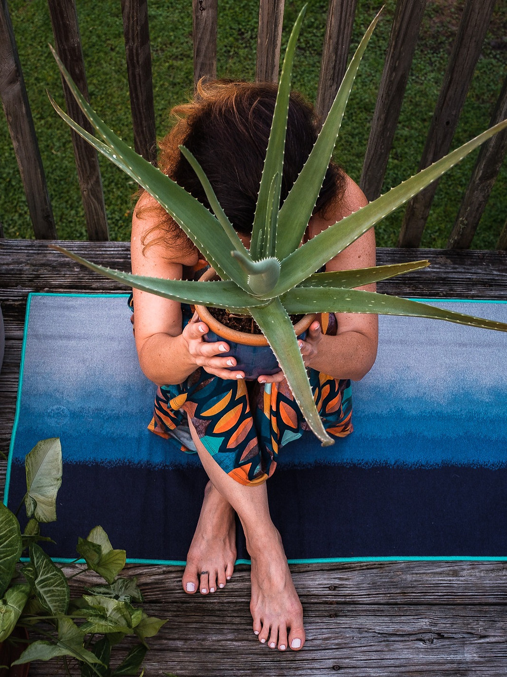 Woman holding a potted aloe plant as part of a health and wellness self care DIY manicure and pedicure for personal brand photography.