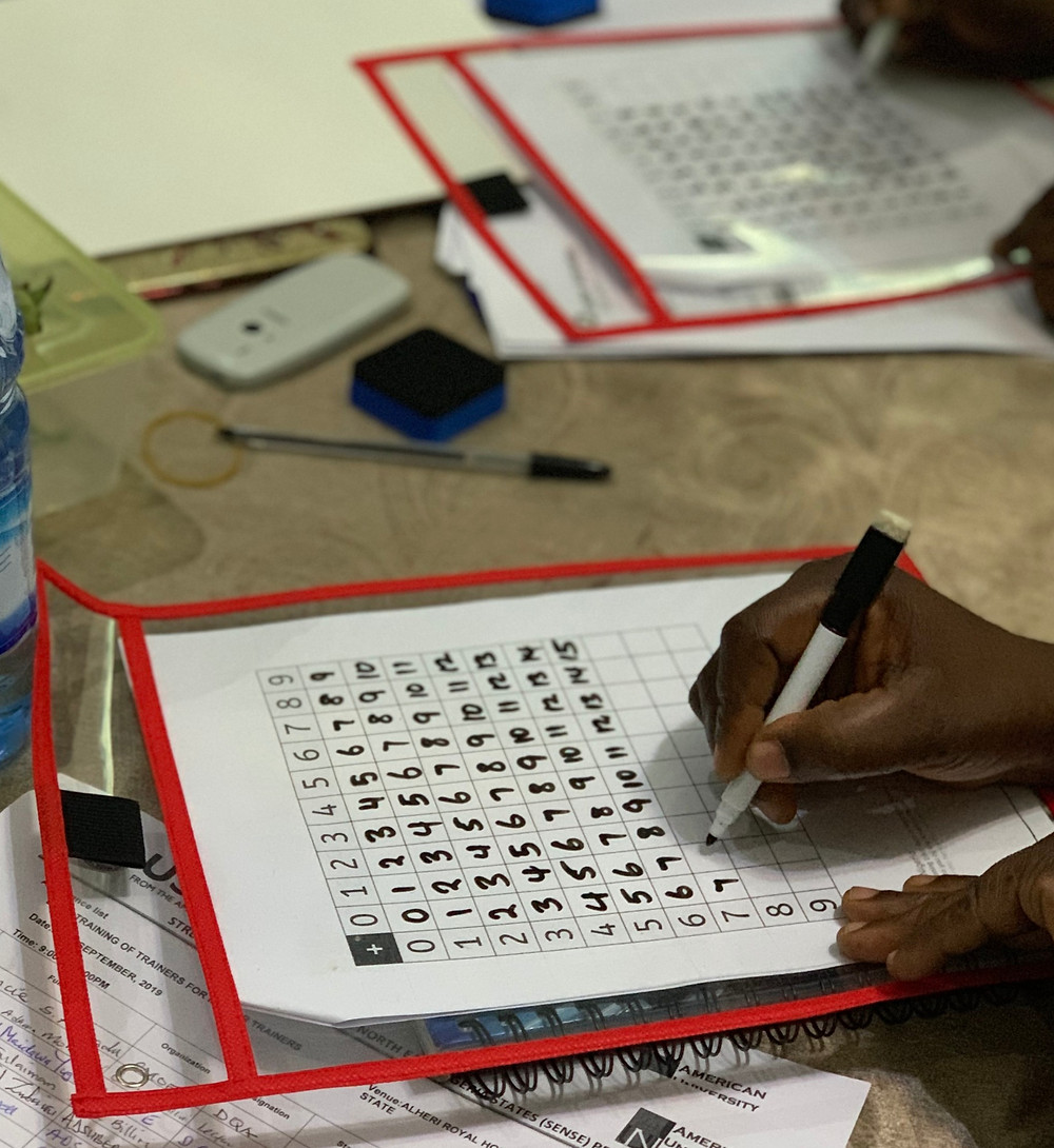 Nigerian teachers testing out laminated pockets by filling in multiplication tabless