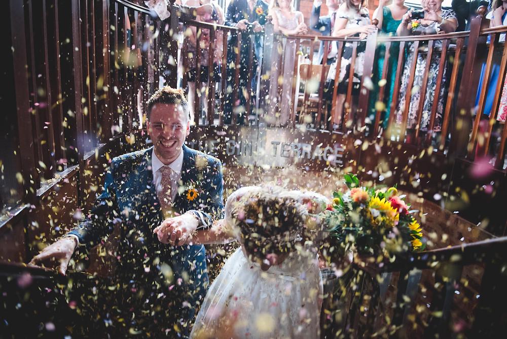 Bride and groom at Birmingham Distillery wedding with flower confetti raining down on them