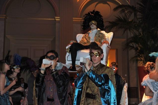 Gekostumeerde lakeien dragen Baron naar het Bal. Kostuums: Avothea.