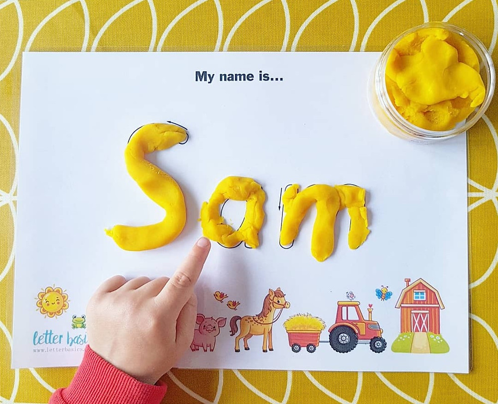 child pointing at name made from yellow playdough