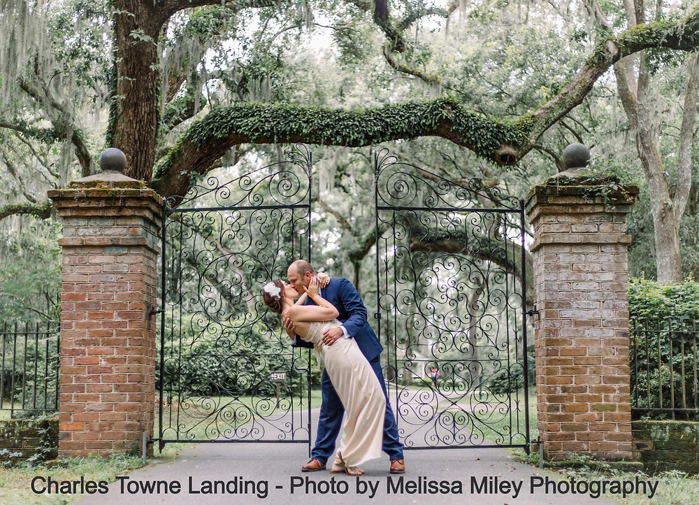 Bride and groom kiss in front of the iron gates of Legare Waring House at Charles Towne Landing