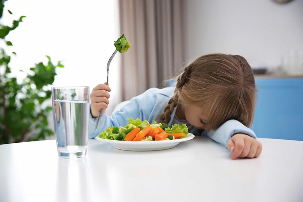 Девојче тажно ја потпира главата на маса до чинија со брокула, додека во раката држи виљушка со парче брокула.