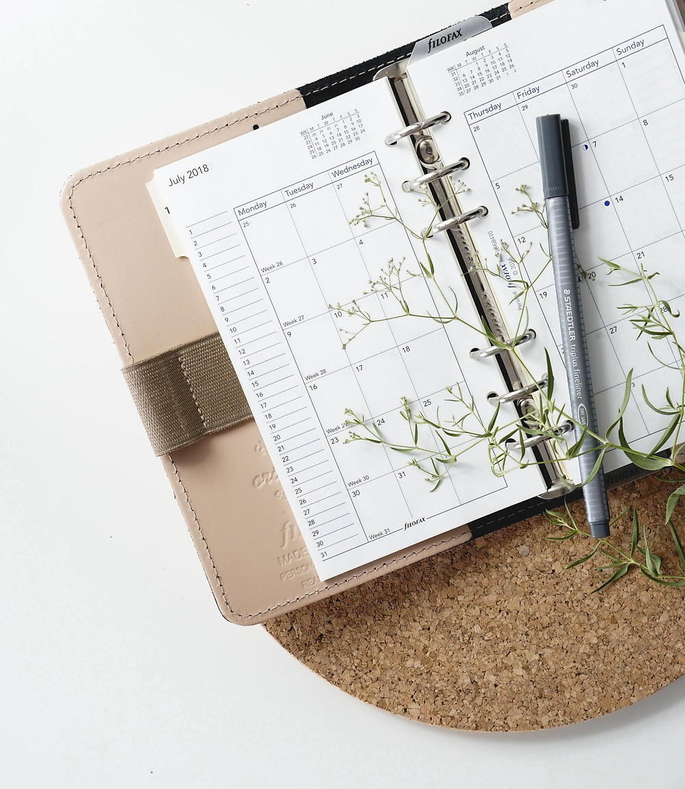 maintaining a writing schedule. calendar. a pen on a diary