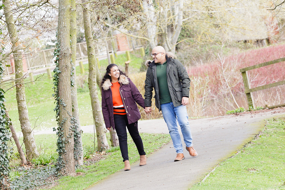 couple walking along a pathway in a park beside a lake in the sunshine