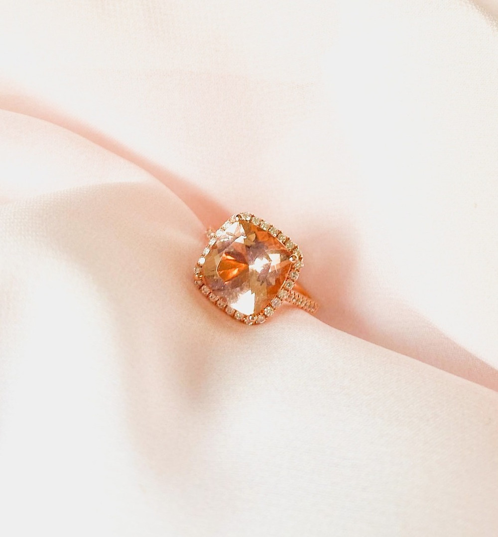 square cushion cut peach pink morganite cocktail engagement ring in rose gold with diamond halo and diamond shoulders on pink peach silk background by Tsarina Gems