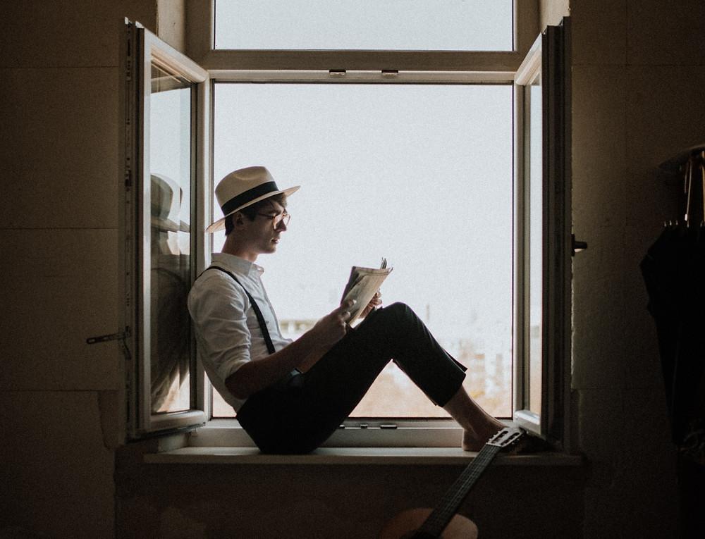 Hombre leyendo en la ventana