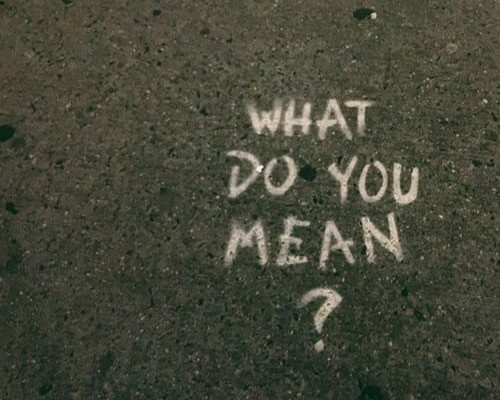 "Sidewalk with, ""What do you mean?"" written on it."