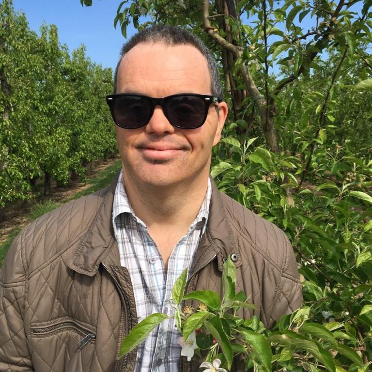 Man met een beperking staat in een boomgaard in het zonnetje