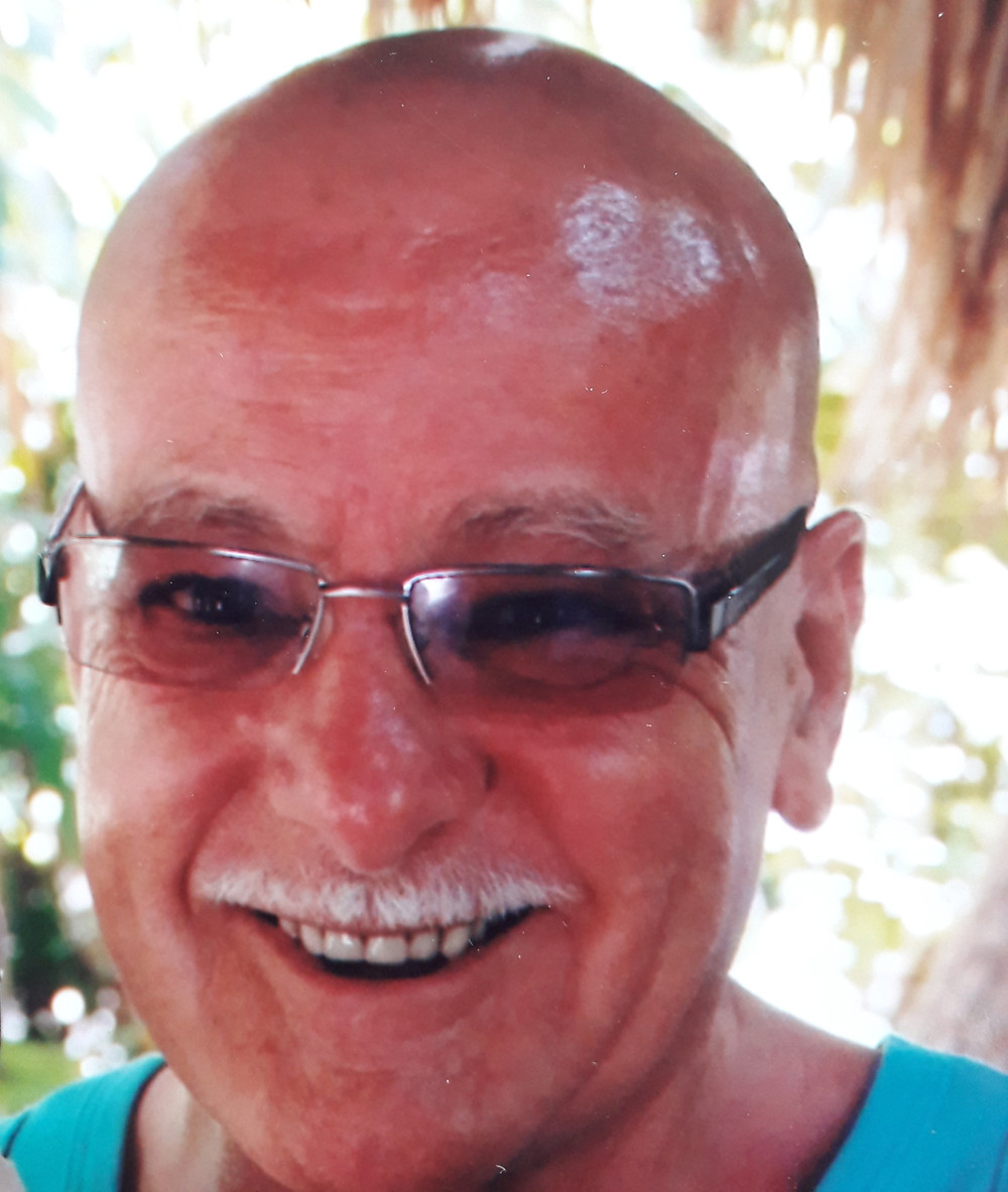 Head shot of James Wyatt. He is smiling and wearing glasses. He has a thin white moustache and is wearing a blue T-shirt