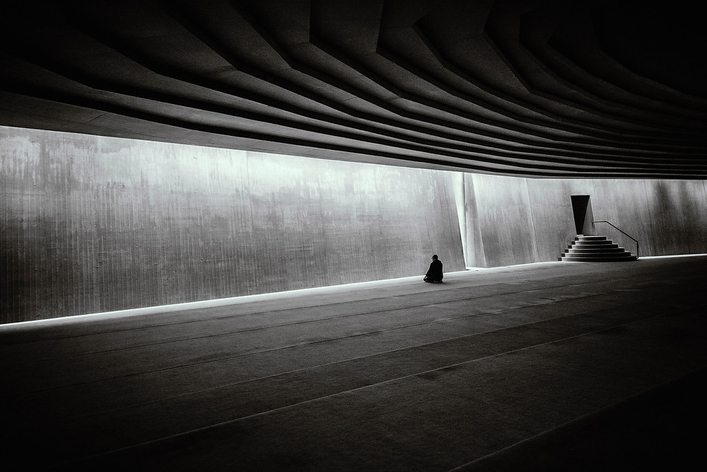 Person meditating in a huge, empty space