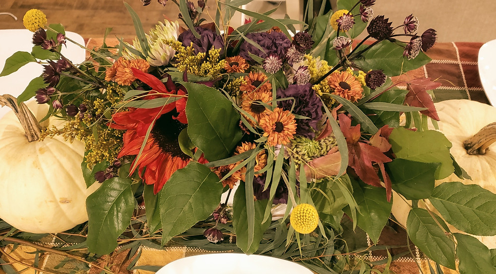 Flower arrangement using sunflower, billy balls and mums.