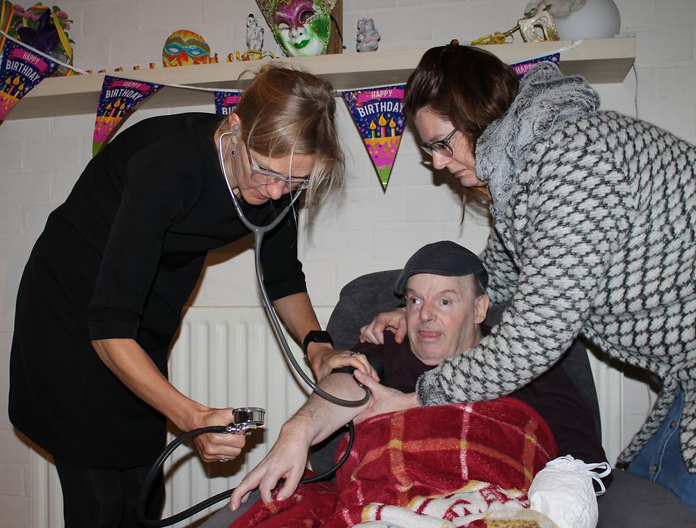 De dokter en verpleegster meten de bloeddruk van een bewoner die in zijn zetel zit