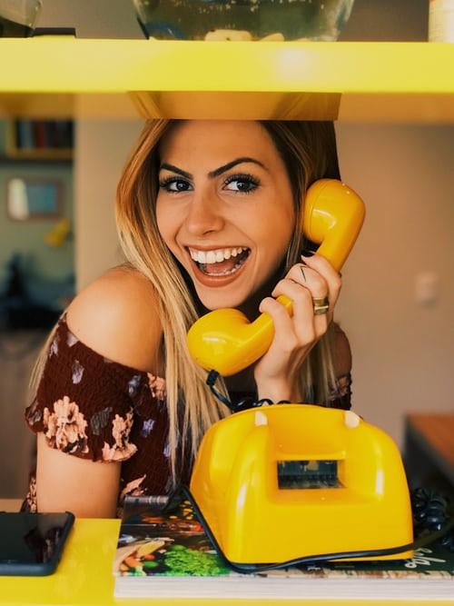 Femme heureuse parle au téléphone pendant le confinement. Happy at home.