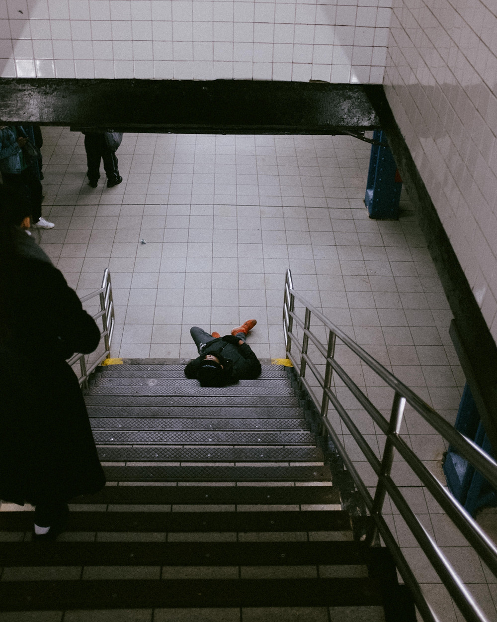A guy lying on the steps to the subway platform, just waiting for his subway.
