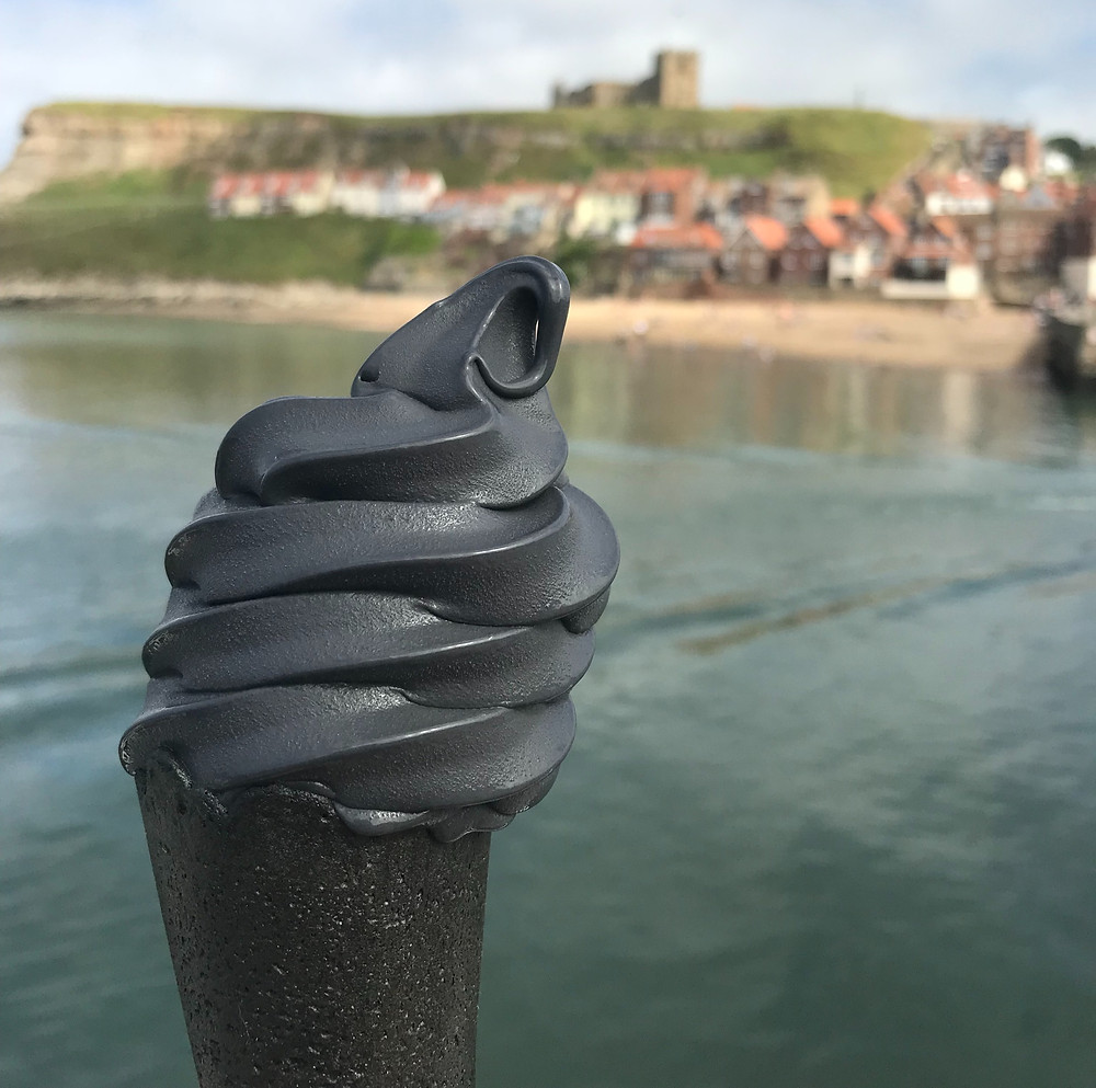 View of Whitby Abbey while holding gothic charcoal ice cream in England