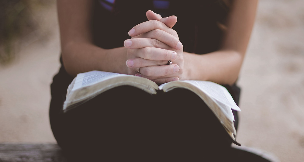 Woman praying over the Bible for understanding of the Scriptures.