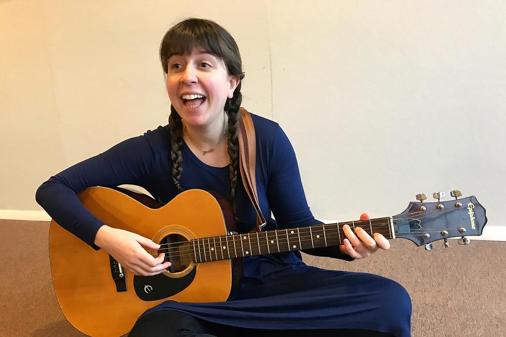 Ms. Joelle plays guitar