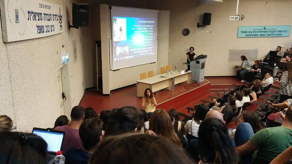 אודיטוריום מלא סטודנטים בבית הספר לעבודה סוציאליות באוניברסיטת תל אביב, ענבל לוי מתרגמת לשפת הסימנים