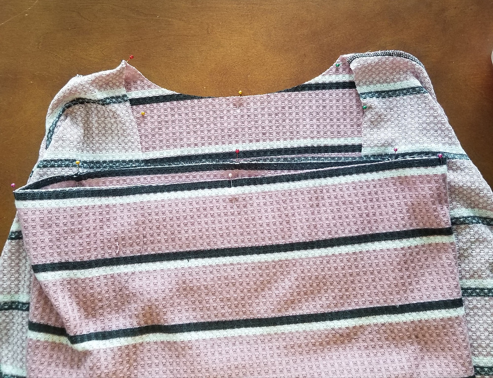 This image shows the shirt inside out with quarter points and shoulder seams pinned. The cowl is laid on top of the shirt with quarter points and seams pinned as well.