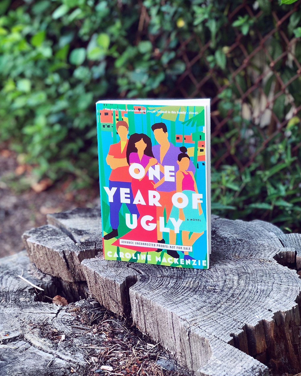 A paperback, advanced copy of One Year of Ugly stands on top of a tree trunk outside, with greenery and a fence in the background.