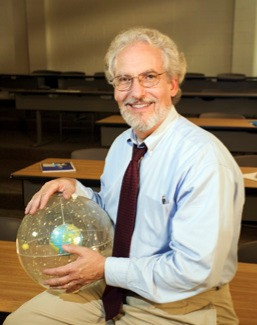 Man holding a clear globe with an earth inside it