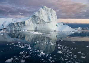 Taken from boat at Disko Bay, Greenland during midnight just after sunset. The calm water creates a nice reflective surface while the fragmented ice make up the whole foreground.