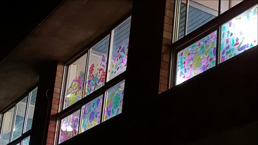 צילום של חלונות חדר האוכל המקושטים בצלופן צבעוני. מסורת שחוזרת על עצמה בכל חג חנוכה