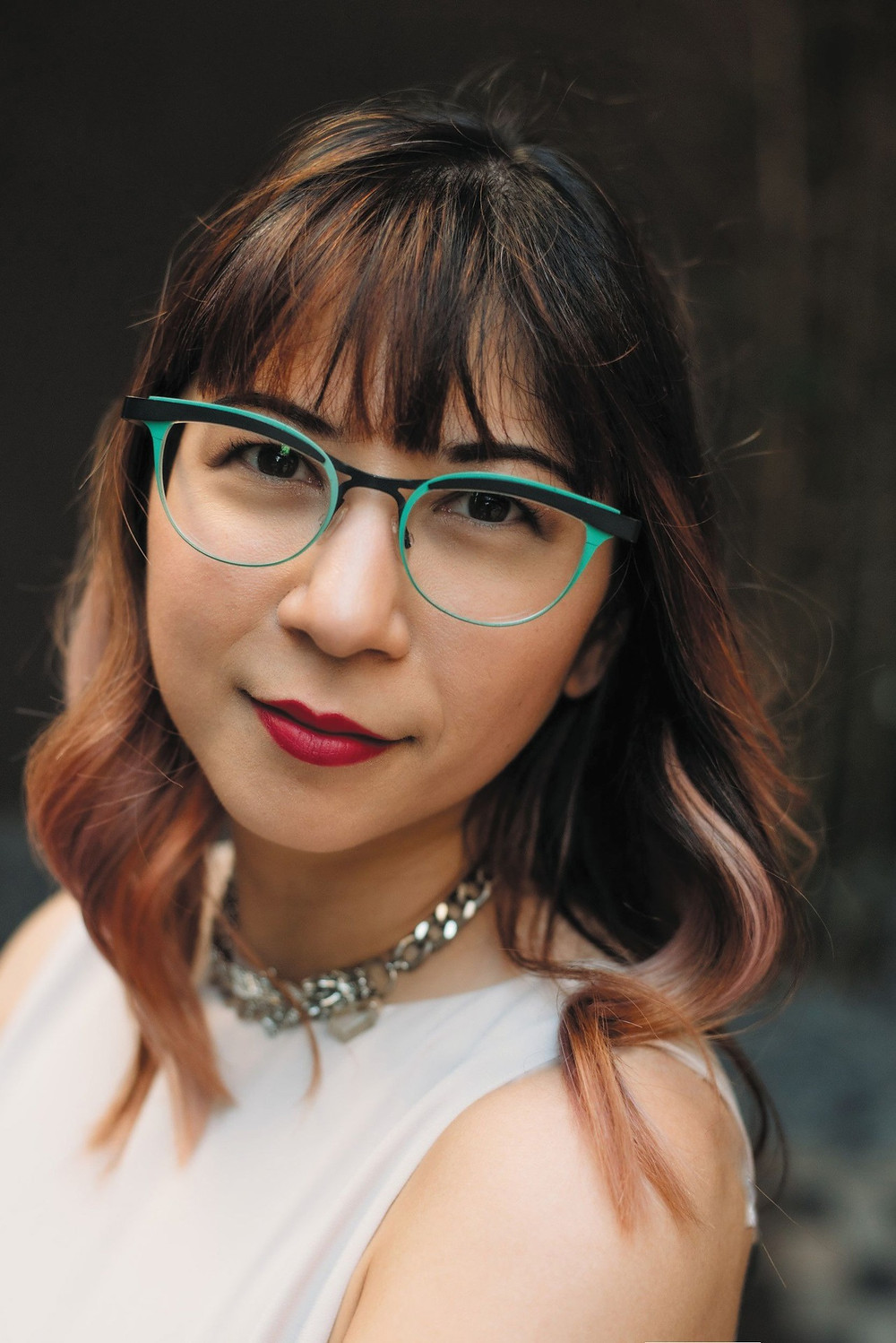 Portrait of a woman looking in camera. Just her head to shoulder area. She has ombre hair, red lipstick, and teal rimmed glasses.
