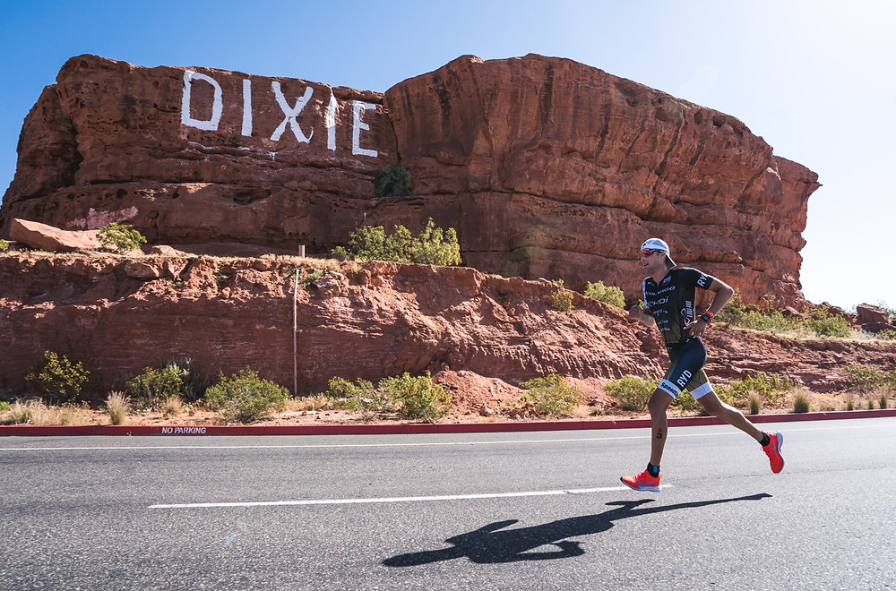 "Pro Triathlete Rudy Von Berg racing 70.3 St. George, running in front of a red rock formation with ""DIXIE"" painted on it."
