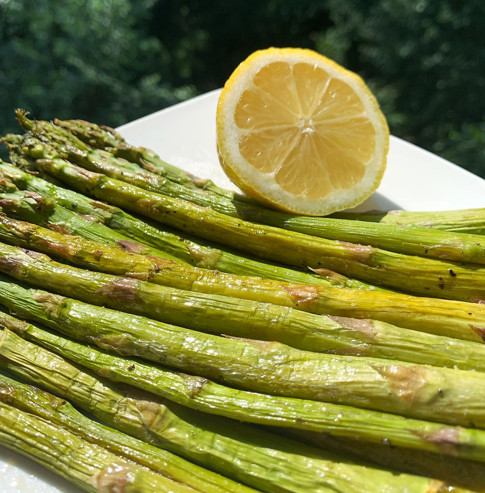 roasted asparagus lined up on a white plate with half of a sliced lemon