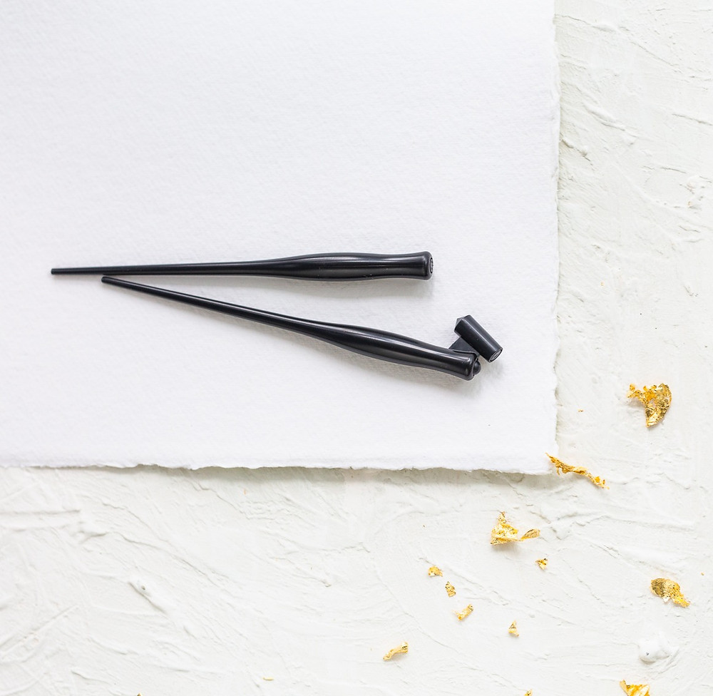 Two black Speedball calligraphy pen holders, placed next to each over on a piece of handmade white Khadi paper