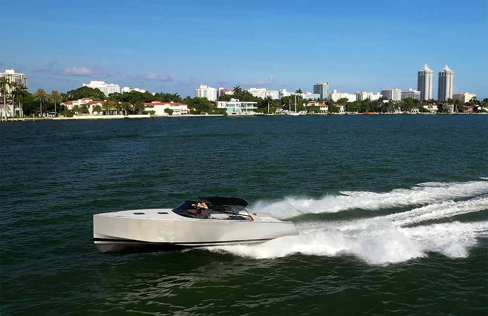 A couple speeds along Miami's Biscayne Bay in a beautiful sleek grey cigarette boat with black piping and half roof. Beautiful Miami Beach mansions and the Blue & Green Diamonds condo buildings can be seen in the background.