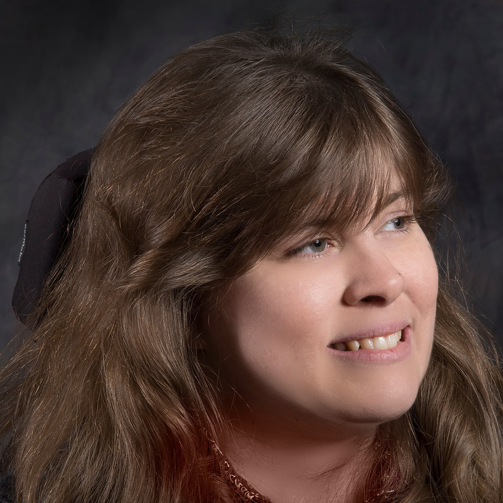 This is a headshot photograph of Jennifer Keelan-Chaffins. She is a beautiful white woman with brown hair and bangs. She is smiling and looking away from the camera.