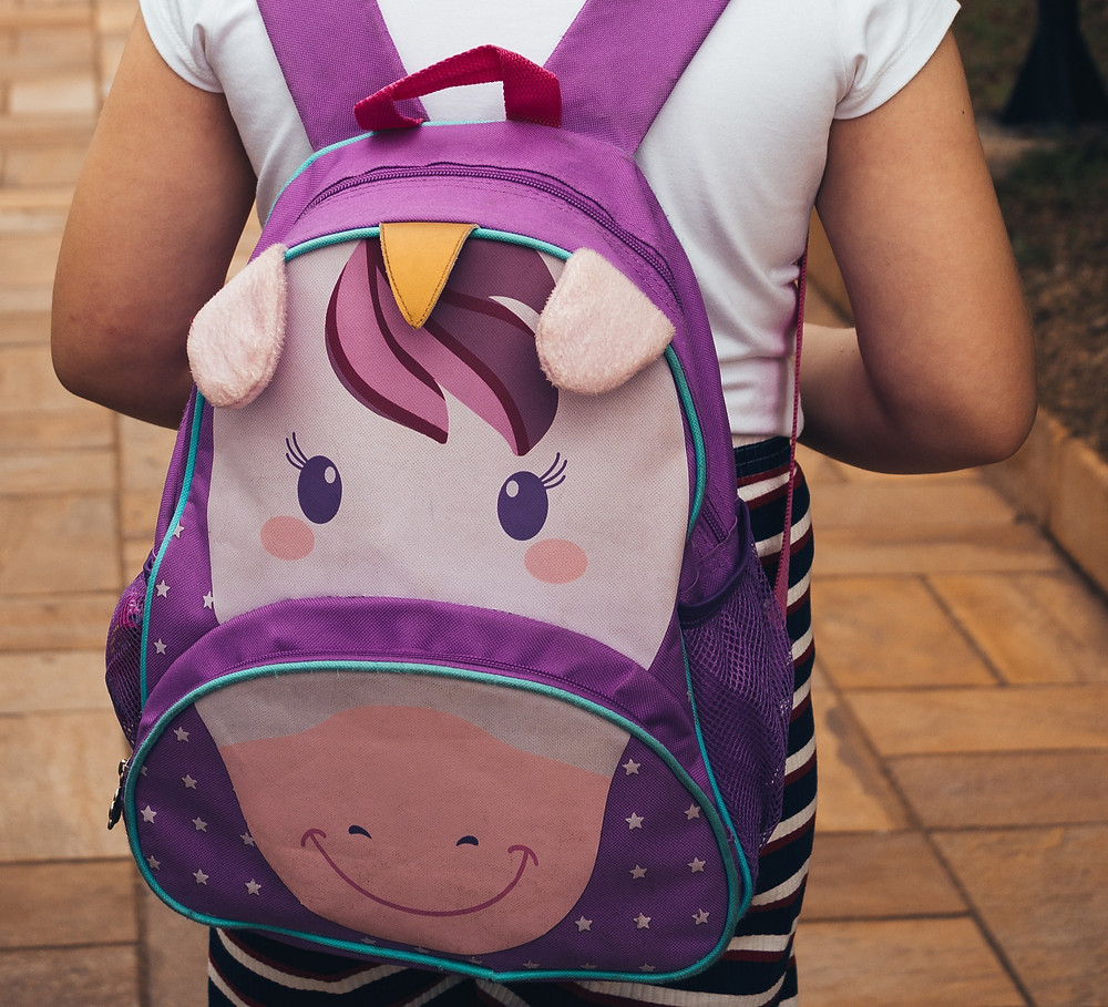 Kid going back to school with unicorn backpack.