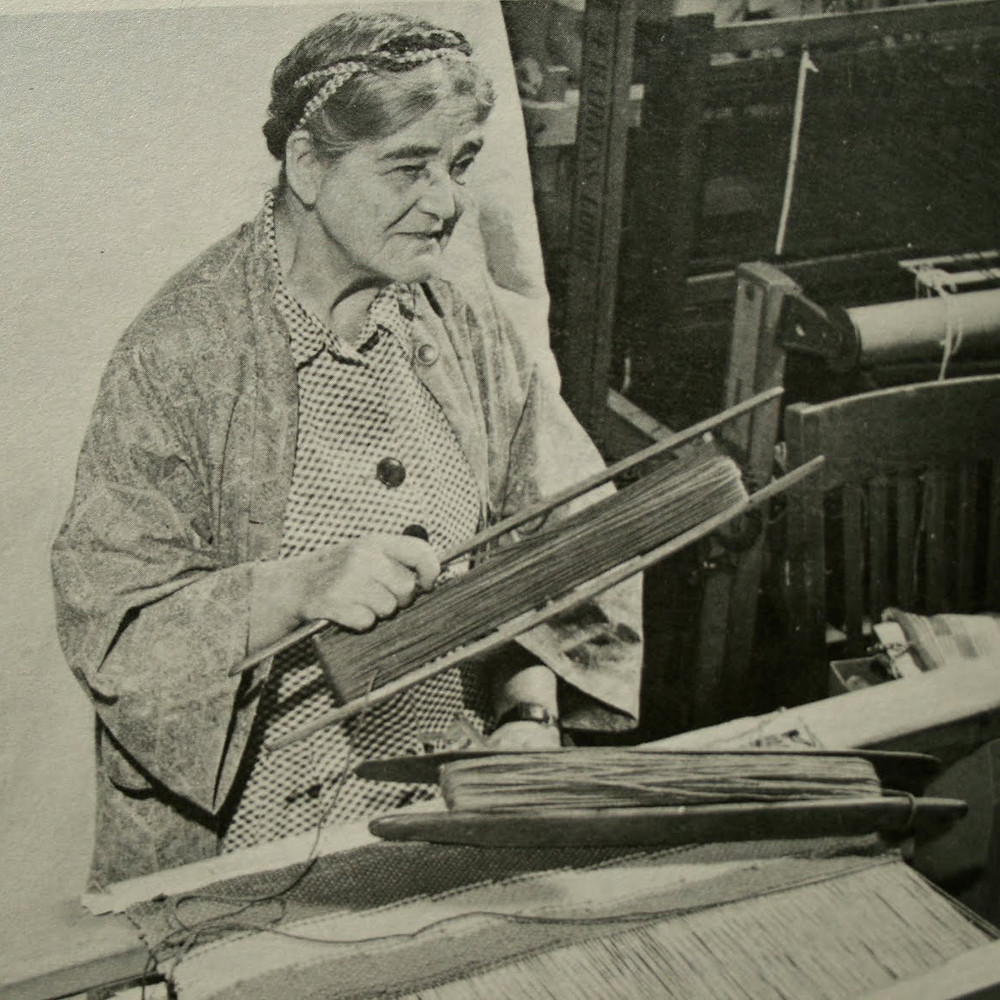 Mary Meigs Atwater seated at a floor loom, holding a large shuttle.