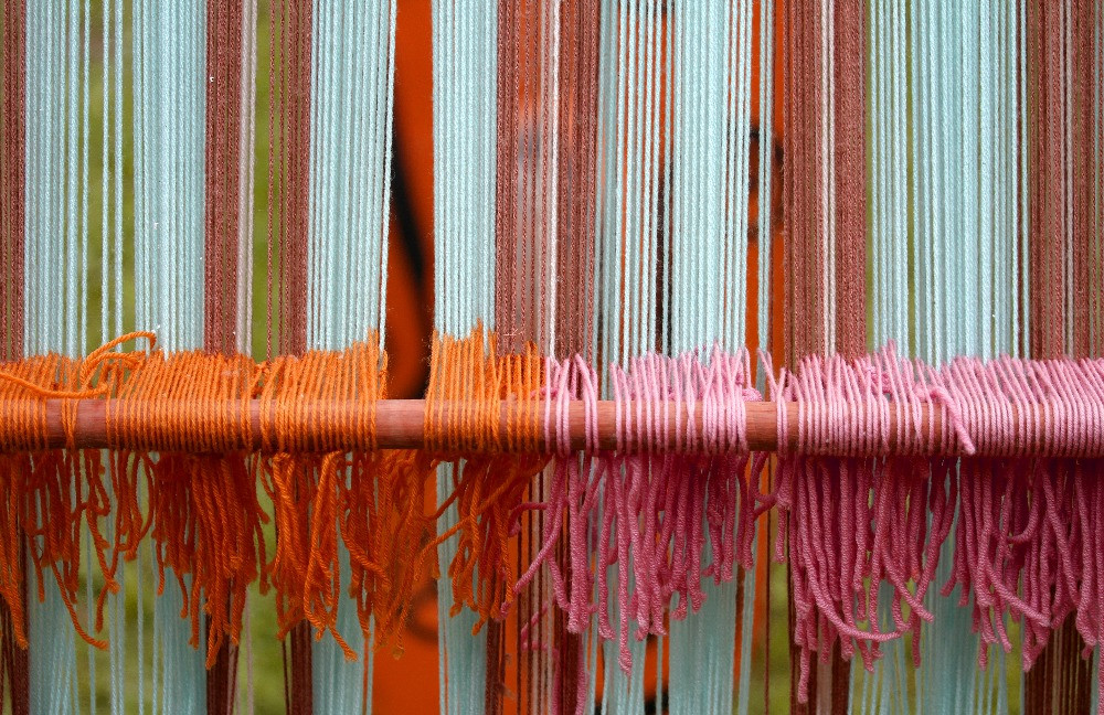 A close up photo of a loom with bright colorful yarn on the loom. There is orange, blue, green and pink shown on the loom. It is ready to be woven into a textile.